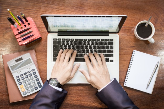 top-view-of-business-man-hands-working-on-laptop-or-tablet-pc-on-wooden-desk_1423-278.jpg